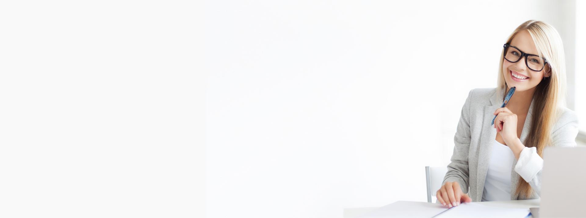 Blonde Frau mit Brille hält einen Kugelschreiber und lächelt fröhlich