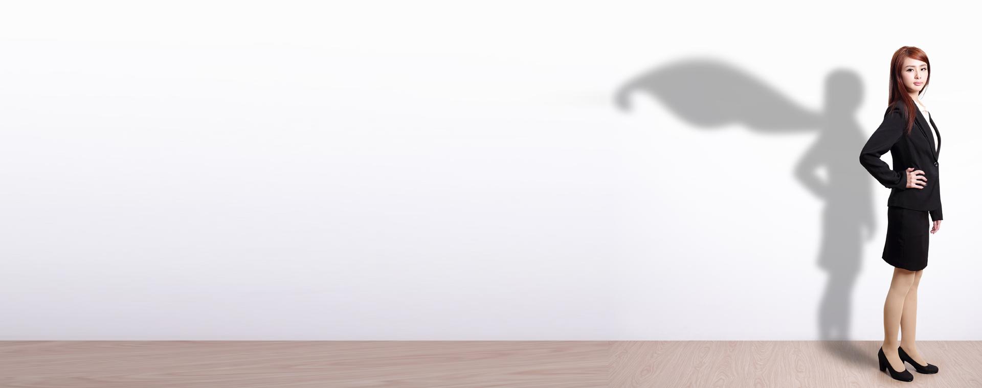 Frau vor Wand mit Schatten in Form eines Superhelden-Umhangs