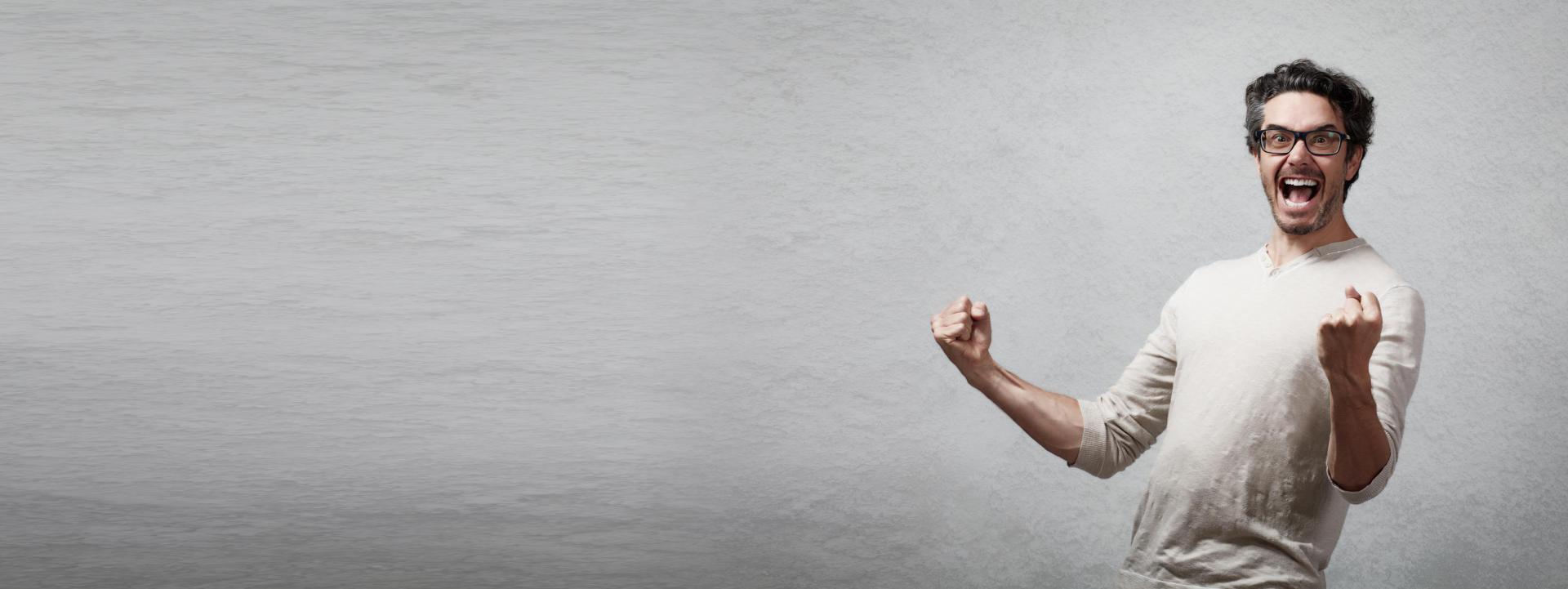 Mann freut sich mit stolz geballten Fäusten vor einer grauen Wand.