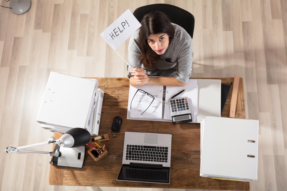 Blick von oben auf eine Frau an Schreibtisch sitzend, zeigt Hilfefahne