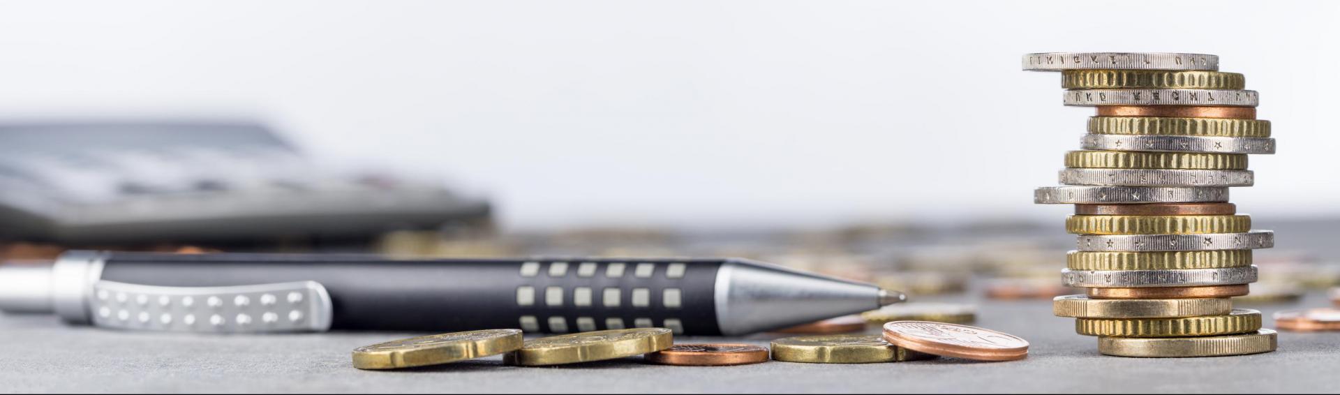 Euromünzen im Stapel und verstreut mit Kugelschreiber und Taschenrechner