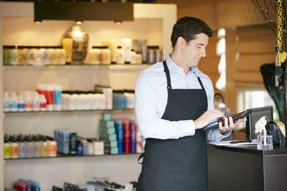 Verkäufer mit Schürze im Geschäft mit Tablet vor einem Verkaufsregal